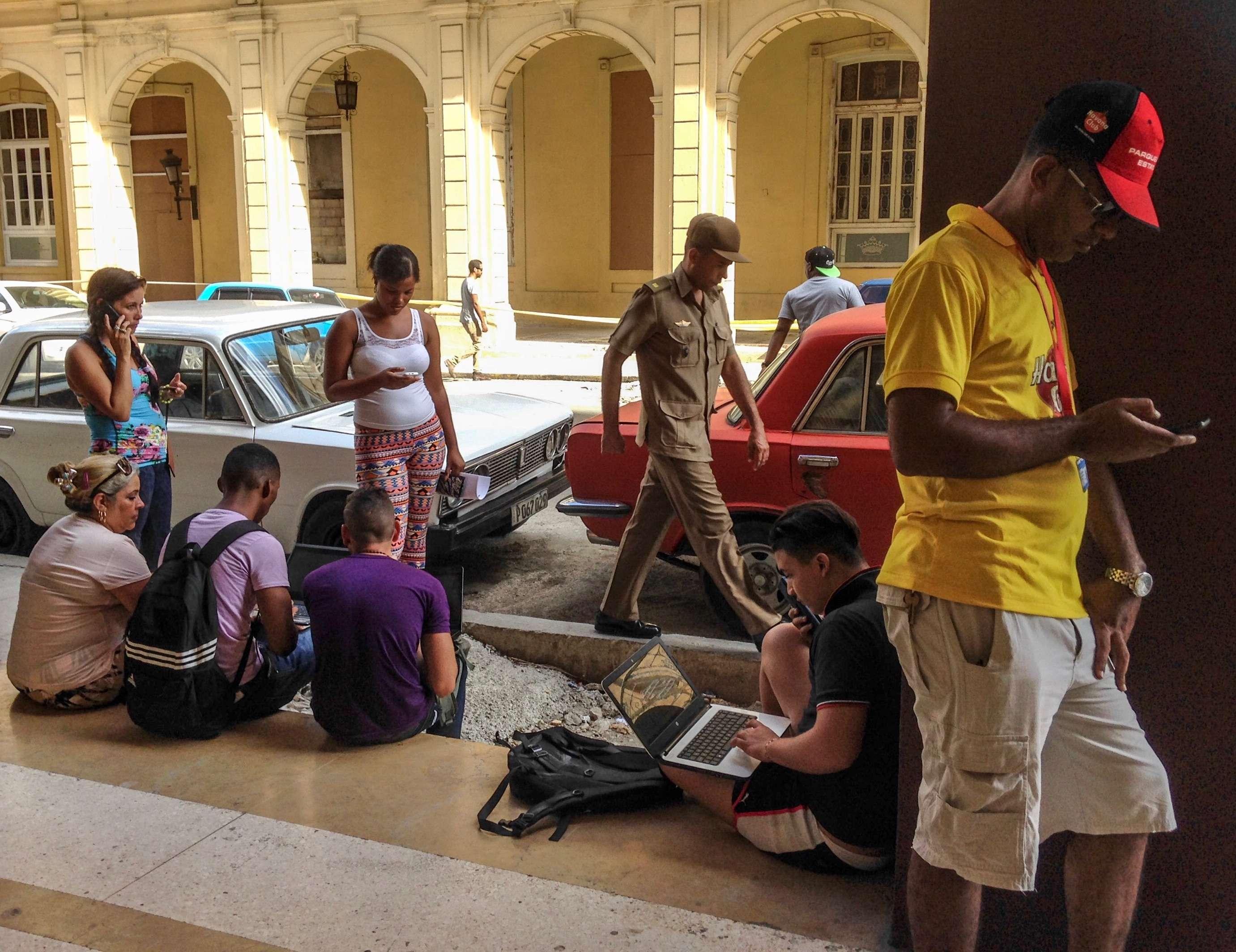 People in a park getting wifi access in cuba