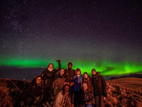 Group under stars and northern lights in Iceland
