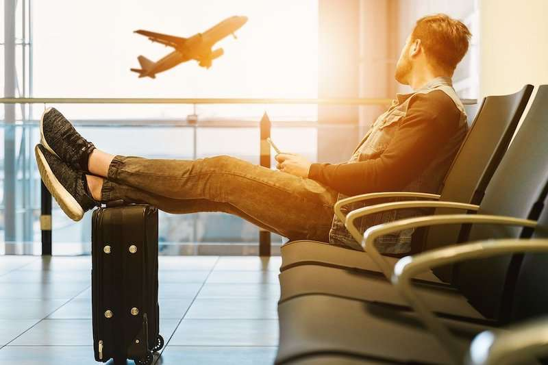 man waiting with suitcase