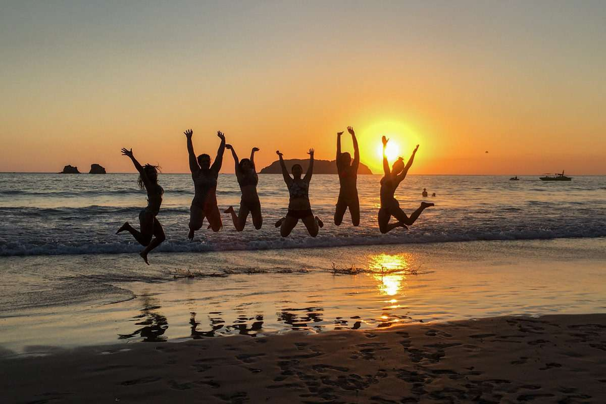 Young adults jumping in front of sunset at the beach